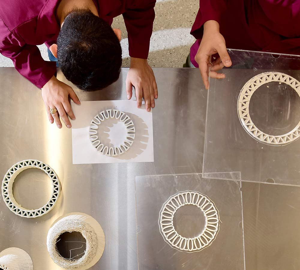 researchers examining 3D printed pieces for prototype structure