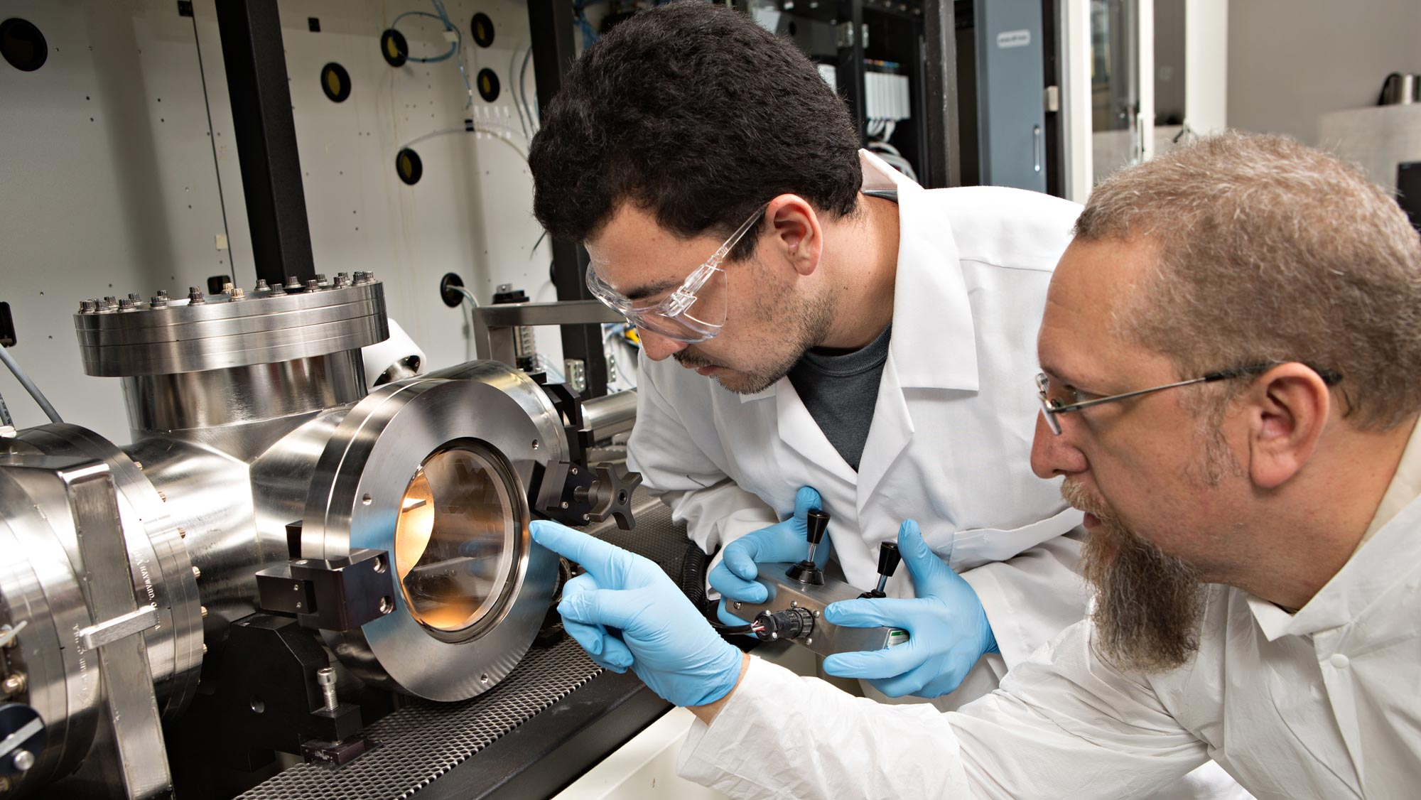 A male researcher with dark hair and goggles and an older male researcher with graying hair and a long beard and glasses observe equipment in a lab.